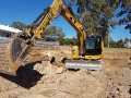 Several trucks and an excavator working on a site cut - Tallebudgera