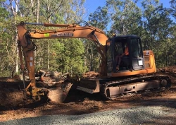 Dean on his 14t digger cutting a house pad - Pullenvale