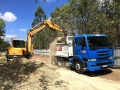 Michael loading the tip truck in his 8t excavator - Crestmead